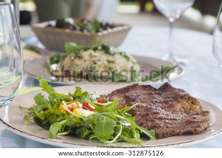 Lunch setting on the table in the restaurant. Focus is foreground, on healthy salad an steak in a plate, while appetizers - risotto and olives are in the background. - stock photo