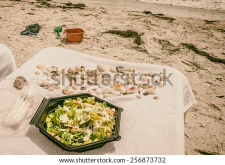 Lunch time on the beach healthy Caesar Salad in plastic box  Caesar salad with chicken served on Luxury Hotel Resort on the beach in Florida Image is filtered - stock photo