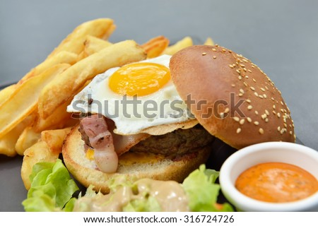 Lunch with burger, chips, eggs, sauce and salad on gray plate from stone slate - stock photo