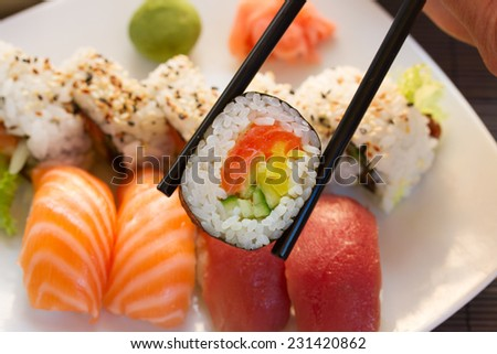 lunch with japaneese  sushi dish  with roll in chopsticks close up  - stock photo