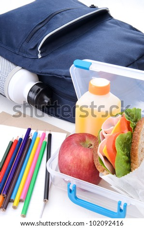 Lunchbox with ham sandwich, apple and oj with schoolbag and water bottle - stock photo