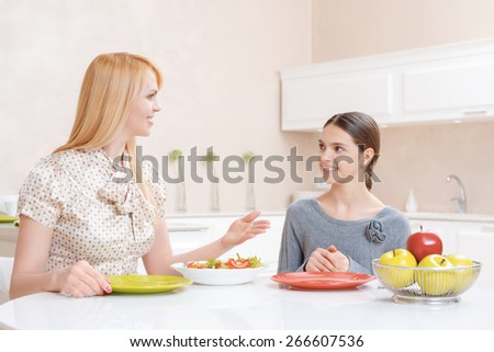 Lunchtime conversation. Charming cheerful mother and pretty daughter talking and eating salad at lunch in the kitchen - stock photo