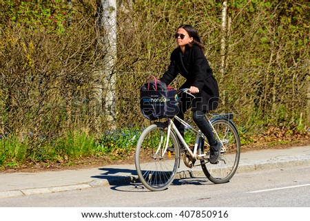 Lund, Sweden - April 11, 2016: Real life in the city. Young adult woman on a bike with her bag in the basket. Street fashion in black coat black trousers.