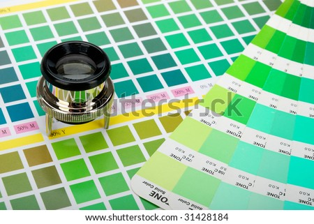 Lupe and a color guide on printed color chart (green, lime and yellow) - stock photo