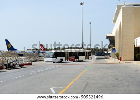LUQA, MALTA - APRIL 18: The bus and building of Malta International Airport on April 18, 2015 in Luqa, Malta. More then 1,6 mln tourists is expected to visit Malta in year 2015.