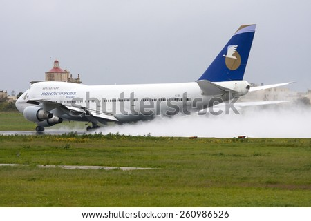 Luqa, Malta February 26, 2011: Hellenic Imperial Airways Boeing 747-230B on take off from runway 31 in rainy weather. - stock photo