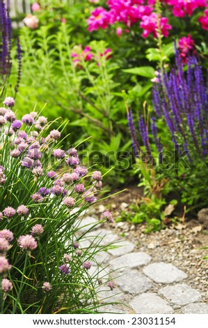 Lush blooming summer garden with paved path - stock photo