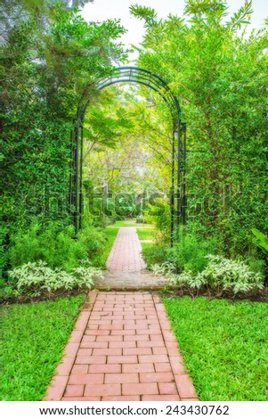 Lush green garden with wrought iron - stock photo