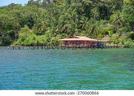 Lush tropical coast with an house and dock over the water in the archipelago of Bocas del Toro, Panama - stock photo