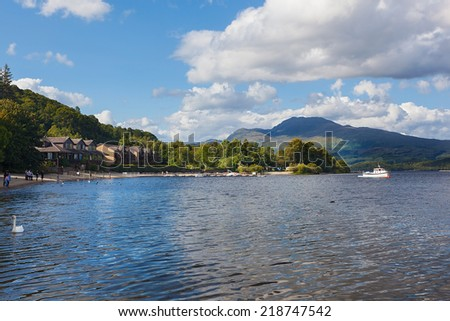 LUSS, SCOTLAND - AUGUST 7, 2014: Houses on the western shore of Loch Lomond by the Luss village. Loch Lomond is the freshwater lake, largest by surface area in all Great Britain.