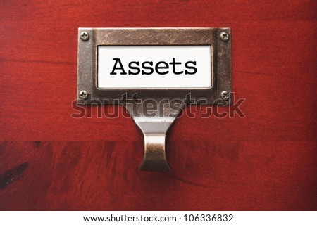 Lustrous Wooden Cabinet with Assets File Label in Dramatic Light. - stock photo