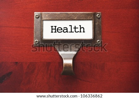 Lustrous Wooden Cabinet with Health File Label in Dramatic Light. - stock photo