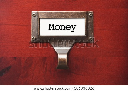 Lustrous Wooden Cabinet with Money File Label in Dramatic Light. - stock photo