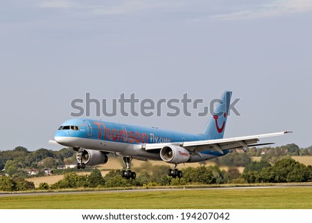 LUTON, UK - SEPTEMBER 13:A Thomson Holidays jetliner lands at Luton airport on September 13, 2013 in Luton. Thomson Holidays,a subsidiary of TUI Travel, was formed in 1965 & floated on the LSE in 1998 - stock photo