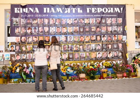 "LUTSK, UKRAINE - SEPTEMBER 24: a mother and daughter mourn the deaths of the ""Heavenly 100"" on September 24, 2015 in Lutsk, Ukraine. ""Heavenly 100"" refers to the 110+ civilian Euromaidan victims. - stock photo"
