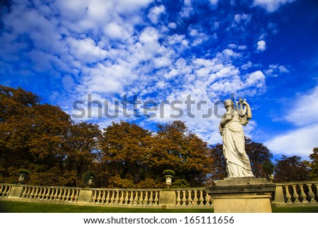 Luxembourg garden in Paris, France. Antique statue illuminated by a sun beam pearcing dramatic autumn sky.  - stock photo