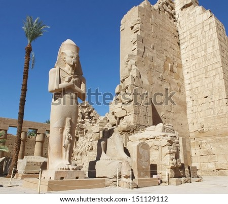 LUXOR, EGYPT-JUN 26:Majestic statue of Ramses II at feet in Hypostyle Hall of Karnak Temple, blue sky and date tree in the background. June 26, 2011. Luxor, Egypt.