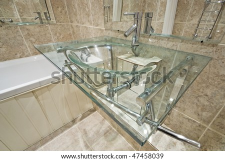 Luxurious bathroom detail with a designer glass wash basin and stone tiled walls - stock photo