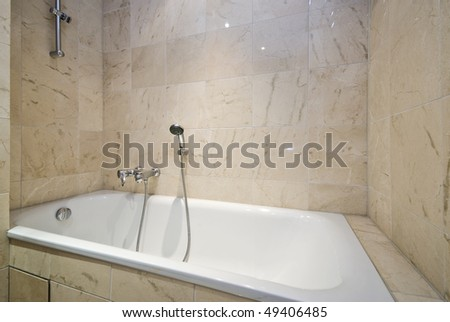Luxurious bathroom detail with a large classy bath tub and stone tiled walls - stock photo
