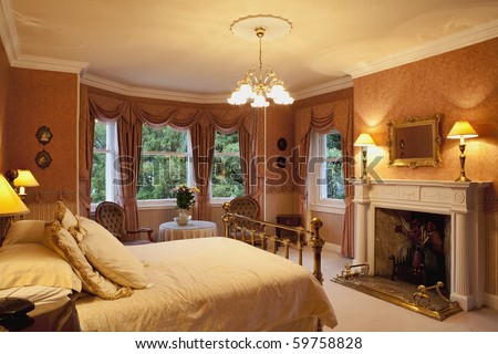 Luxurious bedroom with a fireplace - stock photo