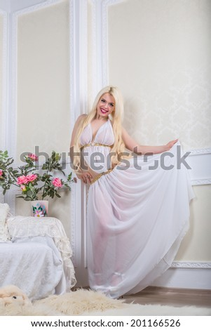 Luxurious blonde woman in a white dress in front of modern classical room - stock photo