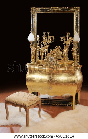 Luxurious bronze interior items. Table, big mirror, lamps, ottoman, clock