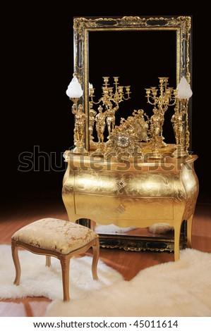Luxurious bronze interior items. Table, big mirror, lamps, ottoman, clock - stock photo