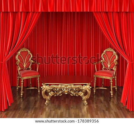 luxurious chairs and a table on stage with red curtains.