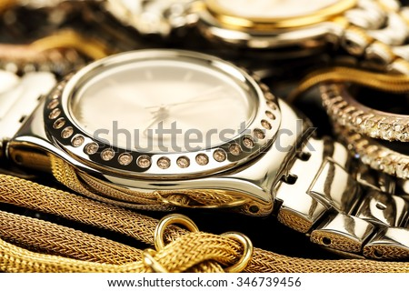 luxurious chrome watch with other pieces of jewelry  - stock photo