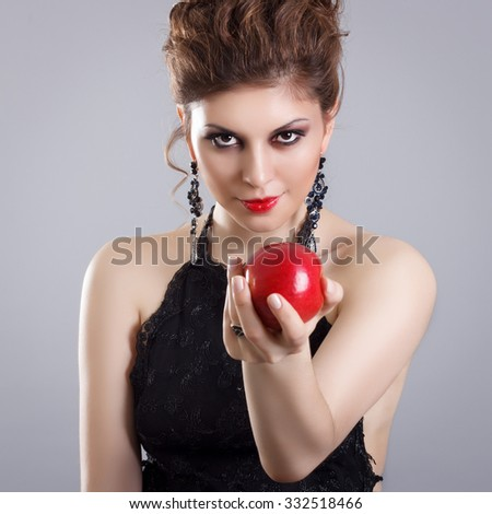Luxurious demonic woman offers a red apple. - stock photo