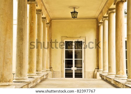 Luxurious entrance between columns. Historic doors to the palace. Classical style. Poland