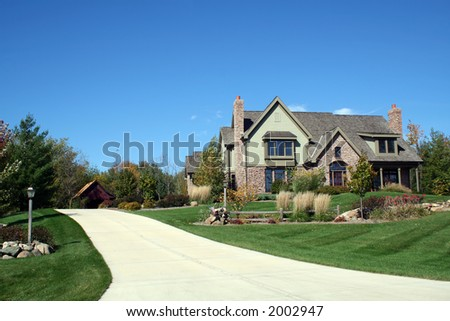 Luxurious executive home with driveway and blue sky - stock photo