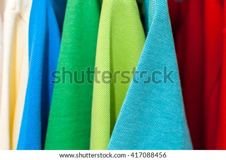Luxurious fine material 100% cotton polo shirts in various colors on hangers - stock photo