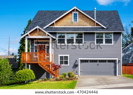 Luxurious gray house with white trim, front stairway and porch. Northwest, USA