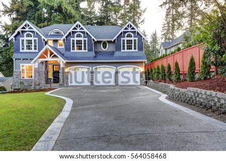 luxurious home exterior with blue vinyl siding and white trim long concrete driveway lead to