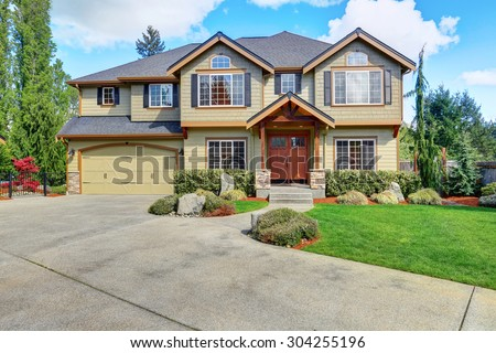 Luxurious home with well kept lawn, and green exterior paint. - stock photo