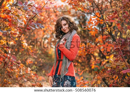 Luxurious lady in colorful dress.A nice, playful smile.A scarf wraps her neck it.Fabulous Golden autumnal trail.Picturesque nature.Fantastic shooting.Fashionable toning.Creative color.