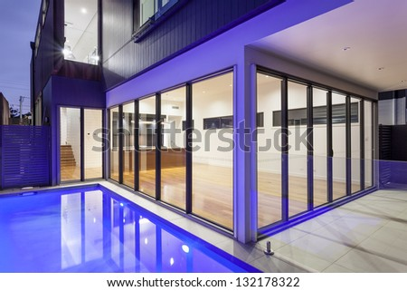 Luxurious modern house with swimming pool and backyard at sunset - stock photo