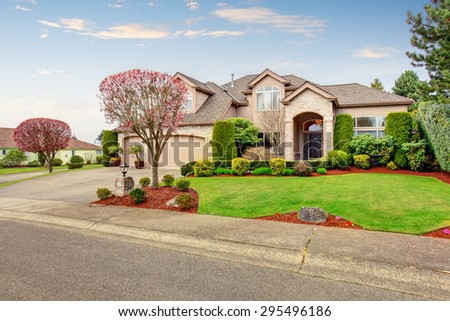 Luxurious northwest home with greenery, garage, and driveway. - stock photo