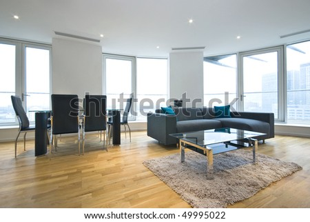 Luxurious open plan living room and lounge with large dining table and modern sofa - stock photo