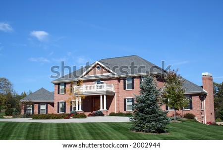 Luxurious red brick executive house with blue sky - stock photo