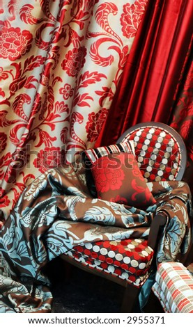 Luxurious red chair with satin pillows and curtains - home interiors - stock photo