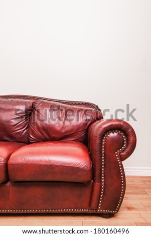 Luxurious Red Leather Couch Detail in front of a blank wall to ad your text, logo, images, etc. - stock photo