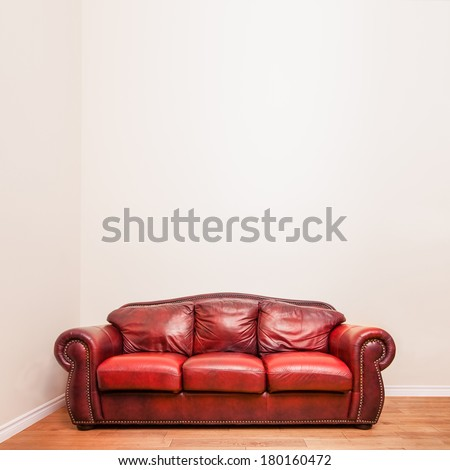 Luxurious Red Leather Couch in front of a blank wall to ad your text, logo, images, etc. - stock photo