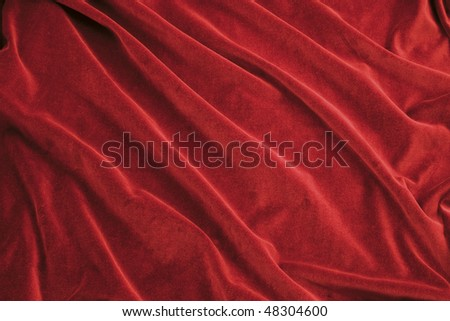 Luxurious rich red velvet folded fabric, useful for backgrounds - stock photo