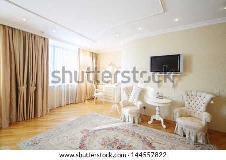 Luxurious room with beautiful armchairs, pier-glass and TV in classic style. - stock photo