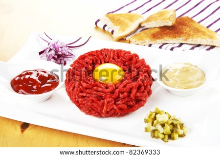 Luxurious steak tartare with yolk on white plate with ketchup, mustard, onion and pickle. Toast bread in background. Gourmet dining. - stock photo