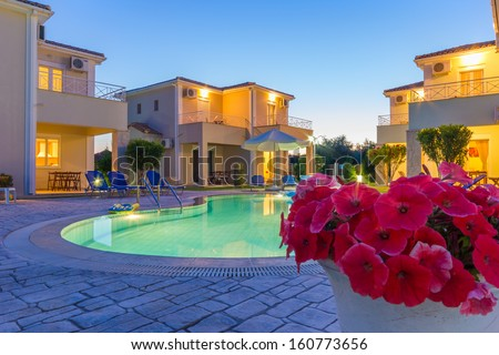 Luxurious villas complex resort with pool in Greece at dusk - stock photo