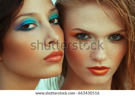 Luxurious weekend.concept. Beautiful couple of fashionable models with perfect arty make-up. Wet hair, waterproof decorative cosmetics. Close up. American disco (vintage) style. Outdoor fashion shot