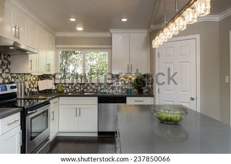 Luxurious white Kitchen in Modern Home with granite counter tops, kitchen island, dark wooden floor and all new new stainless steel appliances. - stock photo